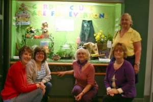 Members of Forever Green Mountain Garden Club, Huntsville District I in front of their display window at the library promoting Garden Club Membership.